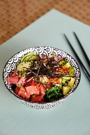 Asian miso soup with raw tuna, avocado, cucumber, onion, sea vegetables, flying fish roe, sesame and ginger in bowl on table in outdoor cafe