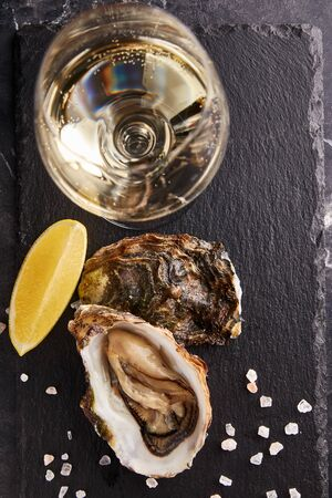 Fresh oysters served with glass of wine, lemon slice and salt on black table