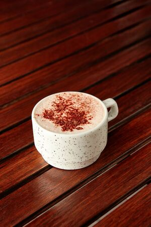 Cup of hot chocolate with milk foam and sprinkled with cocoa on wooden table on brown background. With copyspace. 스톡 콘텐츠 - 131246713