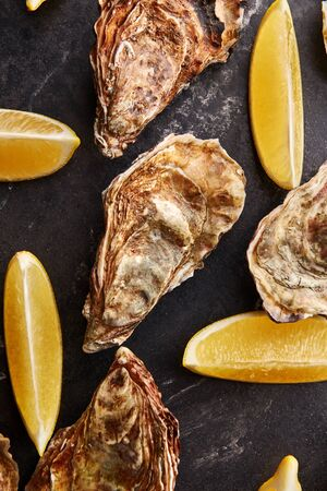 Seafood pattern of wild Netherlands oysters and fresh lemon slices on black marble background, top view. 스톡 콘텐츠
