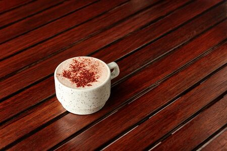 Cup of hot chocolate with milk foam and sprinkled with cocoa on wooden table on brown background. With copyspace. 스톡 콘텐츠
