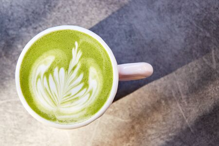 Ceramic cup of matcha latte with beautiful foam on grey background, top view.