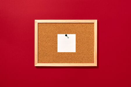 Cork board with wooden frame with one pinned blank note on red background, top view with copyspace.