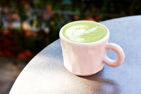 Ceramic cup of matcha latte with beautiful foam on grey background.