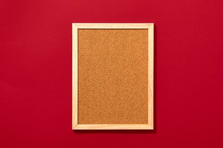 Empty cork board with wooden frame on red background, view from above with place for text. Standard-Bild