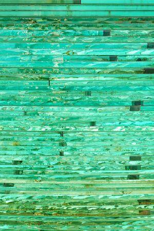 Fondo de vidrio con patrón de rayas en tono de color verde en un día soleado.