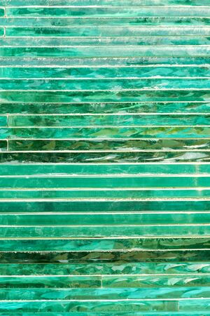 Glass background with stripe pattern in hue of green color at sunny day.