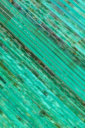 Glass background with stripe pattern in hue of green color at sunny day. Banque d'images