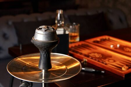Hookah, bottle and glass of whiskey, backgammon board on table in dark bar. Concept of resting together after hard day.