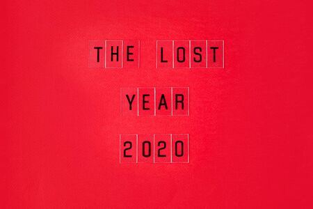 Falling growth in business, composition with The lost year 2020 slogan on red paper background. Flat lay top view, minimal style with copy space.