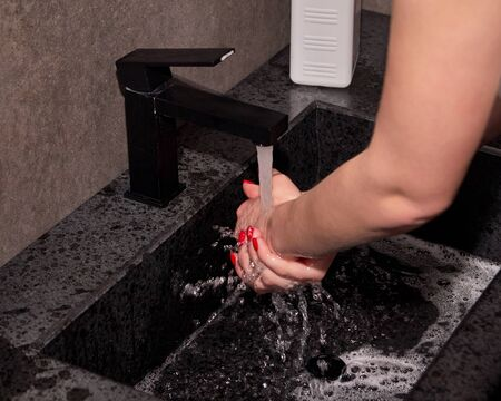 Woman washing hands, rinsing hands under clean running water. Hygiene to stop spreading virus.