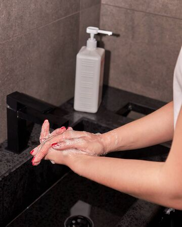 Woman washing hands to get rid of viruses and germs, lathering hands, rubbing them together with soap. 스톡 콘텐츠