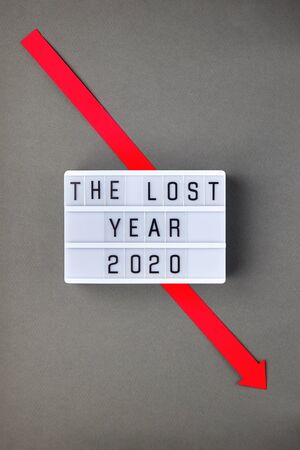 Crisis composition with lightbox with The lost year 2020 slogan and red down arrow on grey paper background. Flat lay top view, minimal style with copy space.