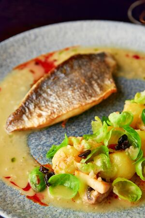 Steamed brussel sprouts, roasted mushrooms, potato, caramelized onion and creamy sauce served with grilled sea bass fillet, healthy dinner.