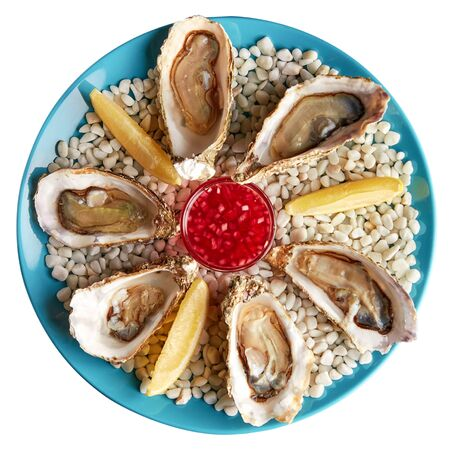 Platter with half-dozen of fresh opened oysters with sauce and slices of lemon on white stones. Isolated over white background.