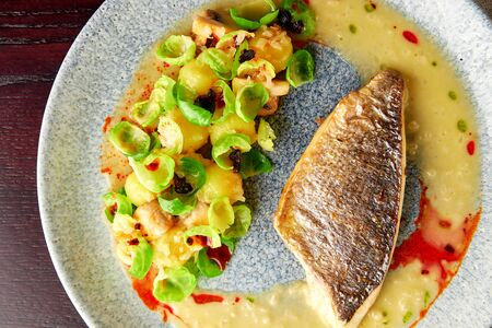 Tasty grilled sea bass fillet served with steamed brussel sprouts, roasted mushrooms, potato, caramelized onion and creamy sauce, healthy dinner. Top view.