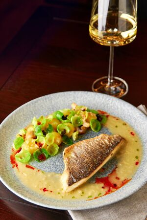 Tasty grilled sea bass fillet served with steamed brussel sprouts, roasted mushrooms, potato, caramelized onion and creamy sauce, served with glass of white wine.