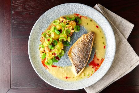Tasty grilled sea bass fillet served with steamed brussel sprouts, roasted mushrooms, potato, caramelized onion and creamy sauce, healthy dinner. View from above with place for text.