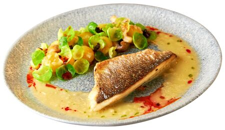 Tasty grilled sea bass fillet served with steamed brussel sprouts, roasted mushrooms, potato, caramelized onion and creamy sauce. Isolated over white background.
