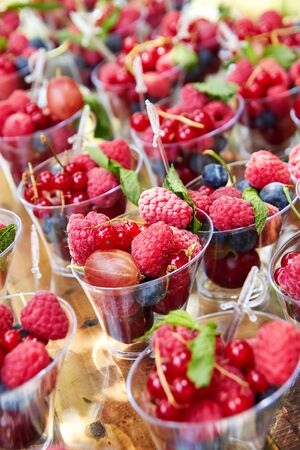 Fresh berries arranged in plastic cups for sale or buffet on wooden table.