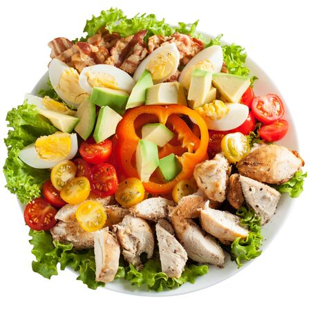 Homemade salad with bacon, chicken breast, avocado, bell pepper, red and yellow cherry tomatoes, romaine lettuce salad, eggs, and olive oil. . Isolated over white background.