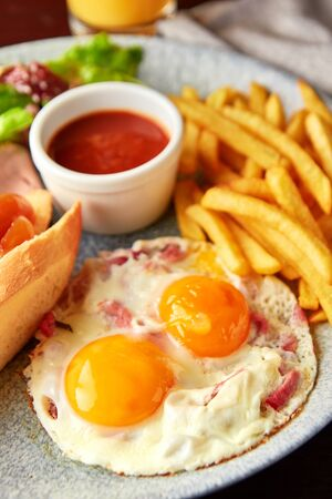 Platter with large breakfast - roasted eggs with bacon, green salad, french fries, bread with cheese and confiture and tomato sauce.