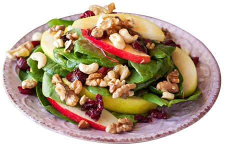 Apple cranberry spinach salad with balsamic vinaigrette. Isolated over white background.