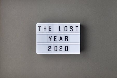 Falling growth in business, composition with lightbox with The lost year 2020 slogan on grey paper background. Flat lay top view, minimal style with copy space.