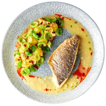 Tasty grilled sea bass fillet served with steamed brussel sprouts, roasted mushrooms, potato, caramelized onion and creamy sauce, healthy dinner. Isolated over white background.
