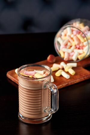 Glass cup of hot chocolate with milk foam and sprinkled with marshmallows on wooden table.