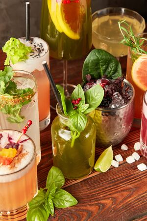 Colorful cocktails in different glasses on wooden table 스톡 콘텐츠