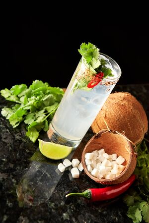 Cocktail with rum, coconut syrup, cilantro, lime and red chilli pepper on black marble bar counter