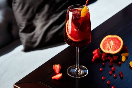 Glass of  cocktail with grapefruit and strawberries on wooden table in cafe