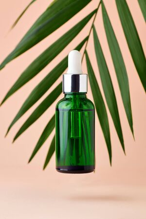 Green dropper bottle with facial essential oil or serum on light pink background with leaves. Natural cosmetic, beauty care or aromatherapy concept.