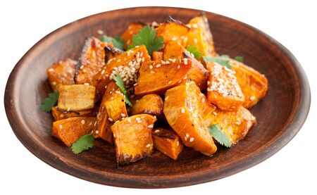 Roasted sweet potatoes with sesame and cilantro leaves. Isolated on white background.