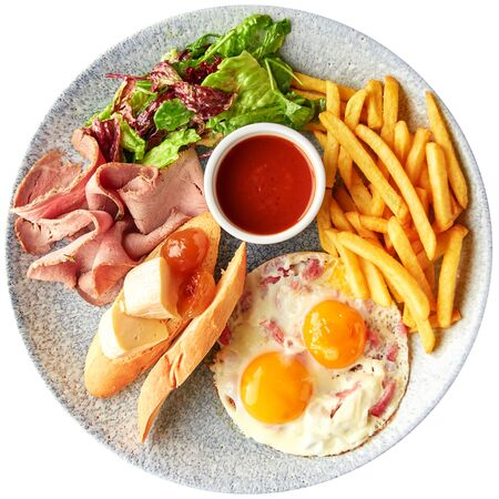 Full English Breakfast including ham, egg with bacon, french fries, lettuce salad, cheese and bread with tomato sauce, top view.