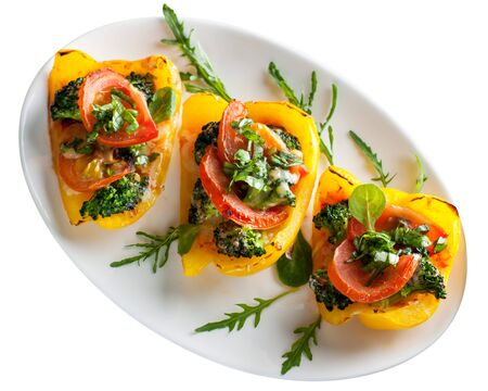 Yellow bell peppers stuffed with tomatoes, broccoli and herbs. Isolated on white background. 스톡 콘텐츠