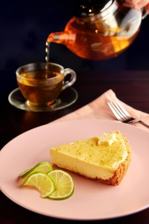 Piece of delicious tart with lime zest and slice of limes on pink plate on dark wooden table, served with cup of herbal tea.