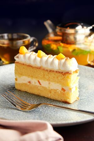Piece of delicious cake with pineapple decorated with whipped cream, served with pot and cup of citrus herbal tea on wooden table.