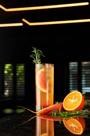 Cocktail with gin, carrot liquor, tonic, orange and rosemary and tonic on black marble bar counter