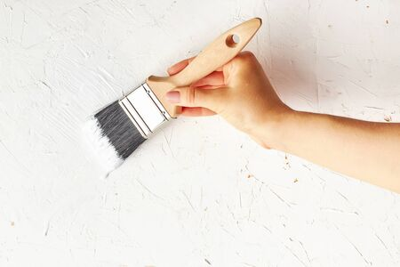 Female hand painting with brush wall surface in white color. Minimalist home repair concept. 스톡 콘텐츠