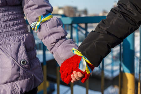 Two people are holding hands. Blue and yellow ribbons are tied in their hands. Symbolic of Ukraine