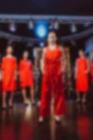 Models on podium, blurred fashion background