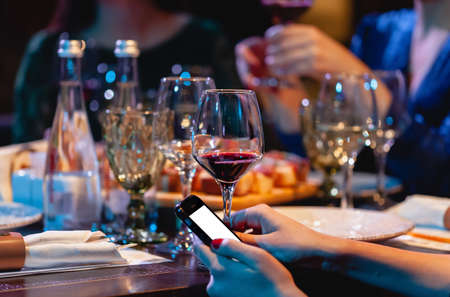 Woman holding a glass of red wine and phone. Dinner at the restaurant, party Foto de archivo