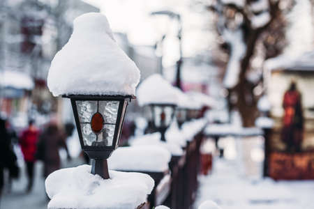 Street lamp in the snow. City background