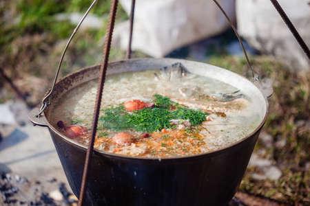 Kulish, kulisz - millet porridge with meat, potatoes, onion, garlic, herbs, salt and spices. Cooking Ukrainian national dish in metal pot on an open fire, outdoor