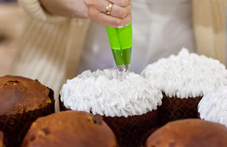 The woman is decorated traditional Ukrainian Easter cake with cream. Paska, Easter bread. Selective focus Stock fotó