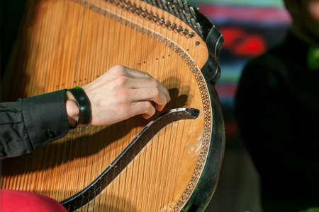 Man playing on Ukrainian national folk instrument bandura. Close up