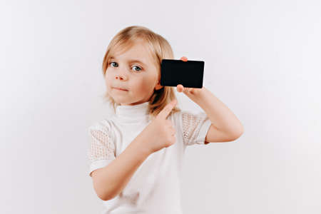 Girl holding black card in hand. Kid showing credit card. Mock up Stock Photo