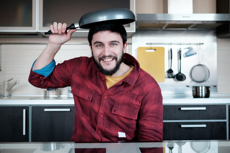 dripping pan: Funny cooking. Attractive caucasian man in the kitchen with dripping pan on his head